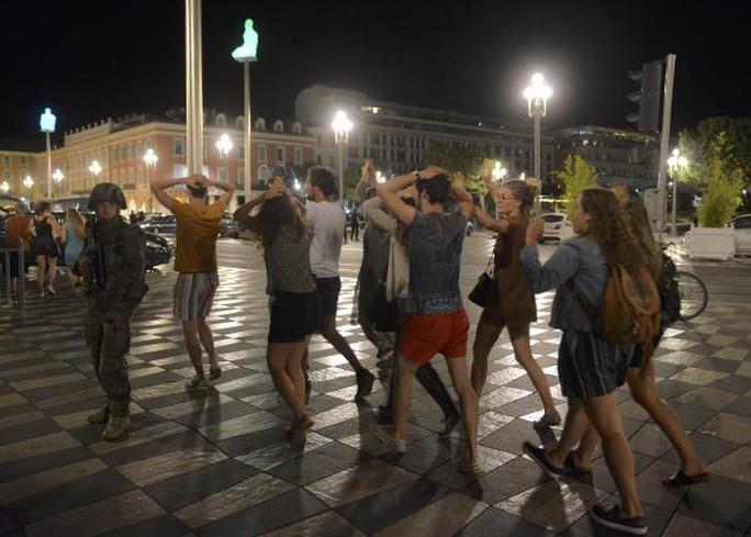 Người qua đường để tay sau đầu trong lúc cảnh sát làm nhiệm vụ trên đại lộ Promenade des Anglais. Ảnh: REUTERS