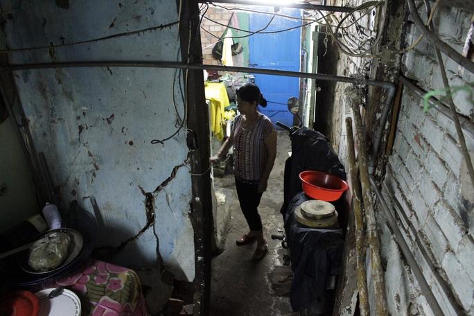 Căn nhà nhỏ chưa tới 20m2 của nhà bà Nguyễn Thị Tuyết Mai (54 tuổi) thuộc diện xuống cấp, hư hỏng nặng nhất khu vực vì bên trong nhà có một cây cổ thụ hơn trăm tuổi mọc giữa nhà, ép sát tường tạo những vết nứt lớn, kéo dài.