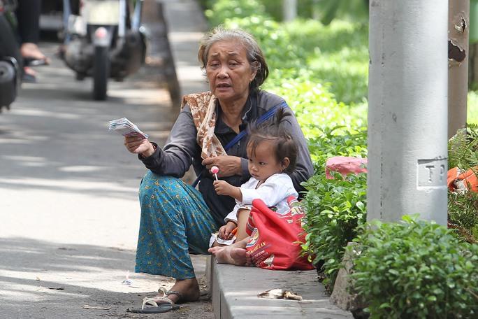 Bà cụ này với xấp vé số trên tay dẫn theo một cháu bé khoảng 2 tuổi mưu sinh tại ngã tư Trương Định - Điện Biên Phủ