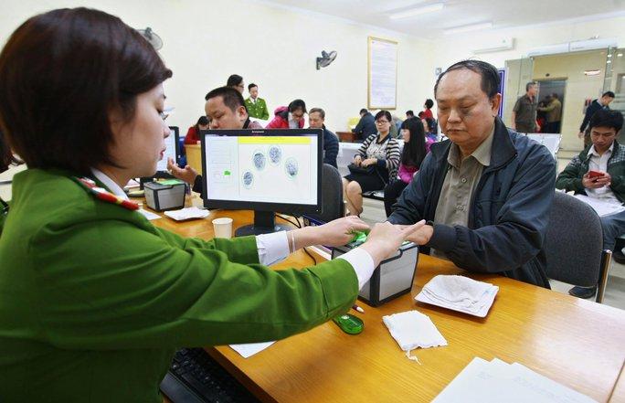 Công an Hà Nội lấy dấu vân tay người đến đăng ký cấp thẻ căn cước công dân Ảnh: TTXVN