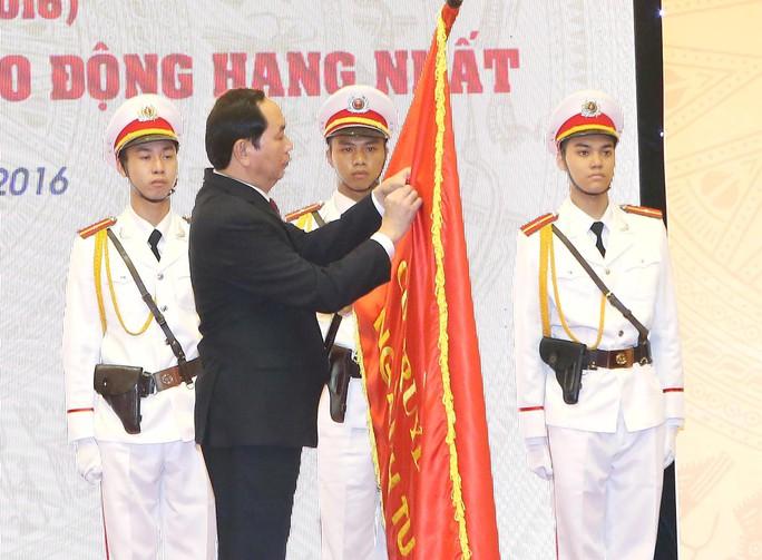 Chủ tịch nước Trần Đại Quang gắn Huân chương Lao động hạng nhất lên lá cờ truyền thống của Tổng cục Thi hành án dân sự Ảnh: TTXVN
