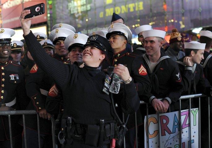 Cảnh sát chụp hình tự sướng với lính thủy đánh bộ và hải quân Mỹ tại quảng trường Thời đại. Ảnh: Reuters