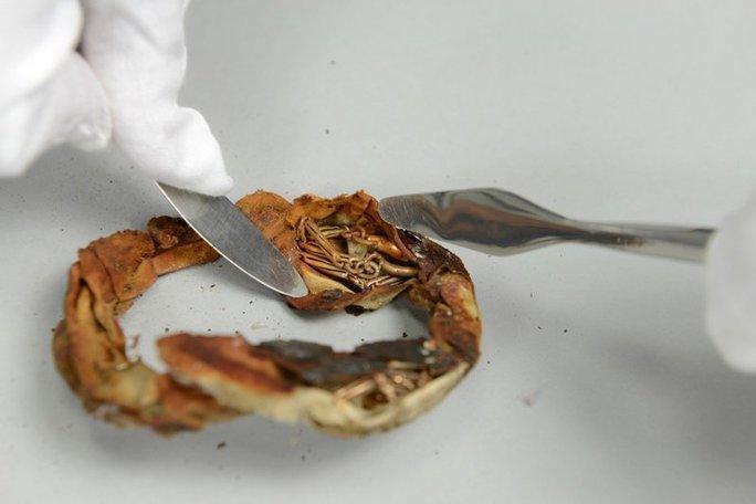Sợi dây chuyền được cuộn rất cẩn thận trong tấm vải trước khi bị giấu dưới phần đáy giả của cốc. Ảnh: Auschwitz Museum