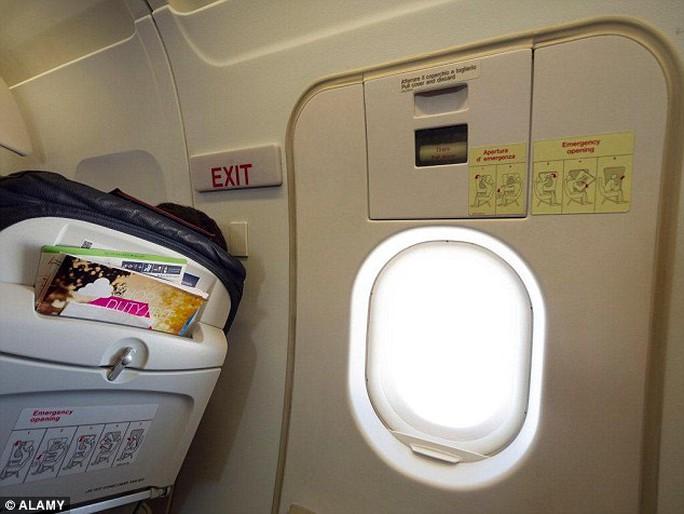 Người phụ nữ cố mở cửa thoát hiểm trên máy bay. Ảnh: Alamy