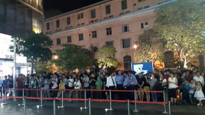 Trong khi ngoài trời đang lắc rắc mưa, phía cổng trước Bitexco hiện vẫn có rất nhiều người chờ đợi. Ảnh: Đình Thi