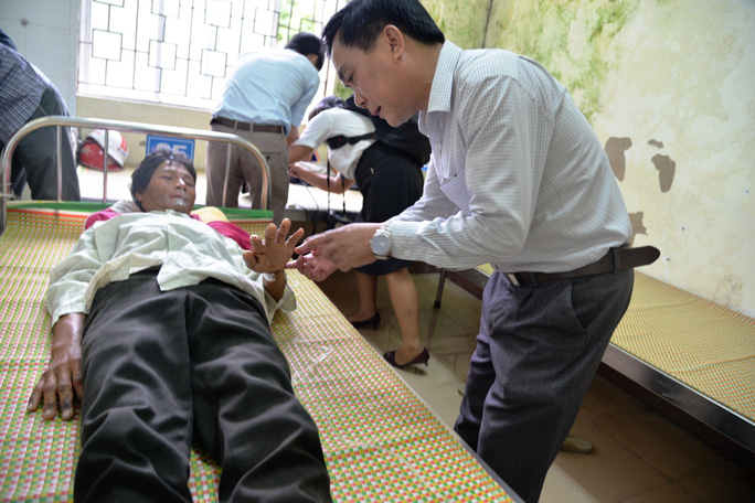 Ông Nguyễn Tấn Đức, Giám đốc Sở Y tế Quảng Ngãi thăm hỏi 2 bệnh nhân mắc Hội chứng viêm da dày sừng lòng bàn tay bàn chân. Ảnh: Tử Trực