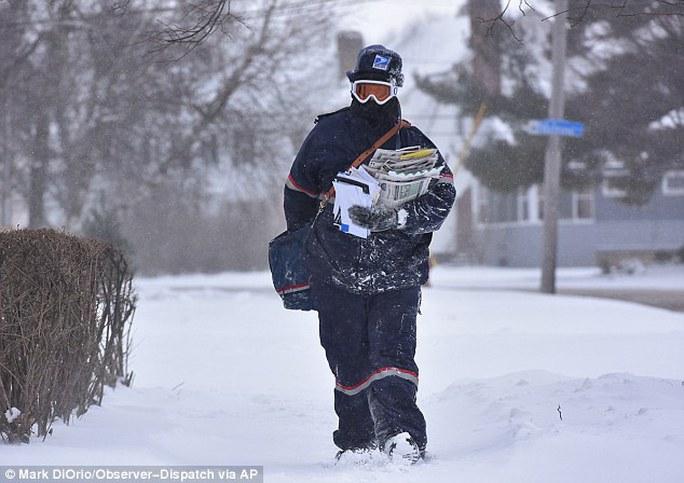 Một nhân viên bưu chính ăn mặc kín từ đầu đến chân để làm việc trong giá rét