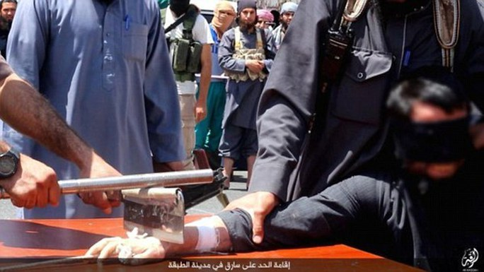 IS dùng một con dao to và thanh sắt để chặt tay phạm nhân. Ảnh: Daily Mail