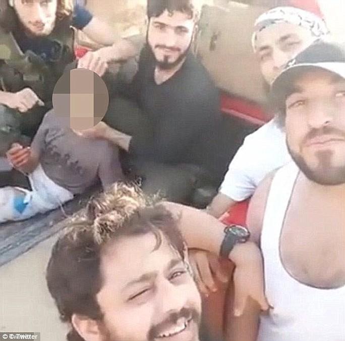 Các tay súng Nour al-Din al-Zenki chụp hính cùng nạn nhân. Ảnh: Twitter