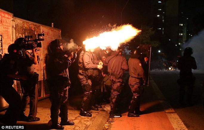 Cảnh sát chống bạo động bắn hơi cay giải tán đám đông. Ảnh: Reuters