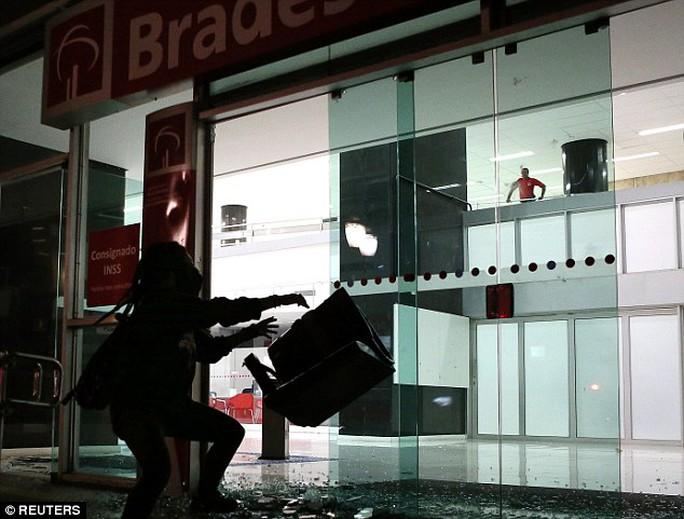 Một người biểu tình quá khích đập phá cửa kính. Ảnh: Reuters
