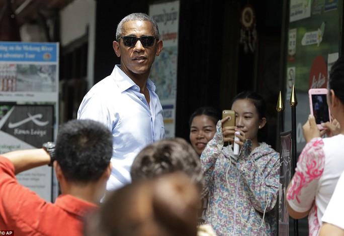 Người Lào tranh thủ chụp hình Tổng thống Mỹ. Ảnh: AP