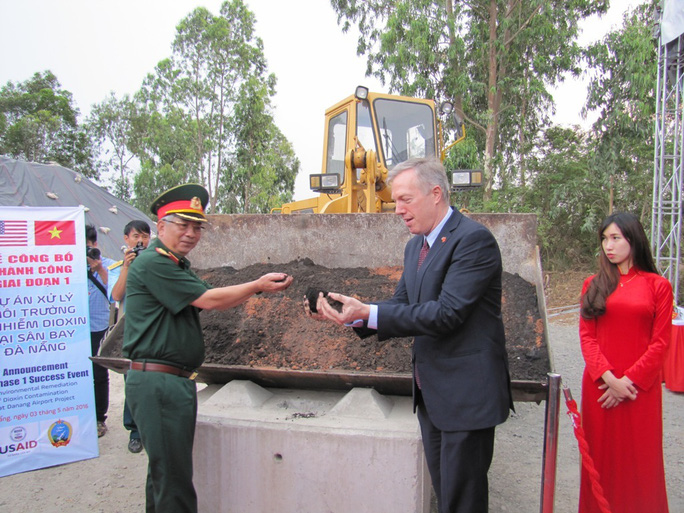 Thượng tướng Nguyễn Chí Vịnh và Đại sứ Hoa Kỳ Ted Osius, lấy tay cầm đất từng nhiễm dioxin đã qua xử lý.
