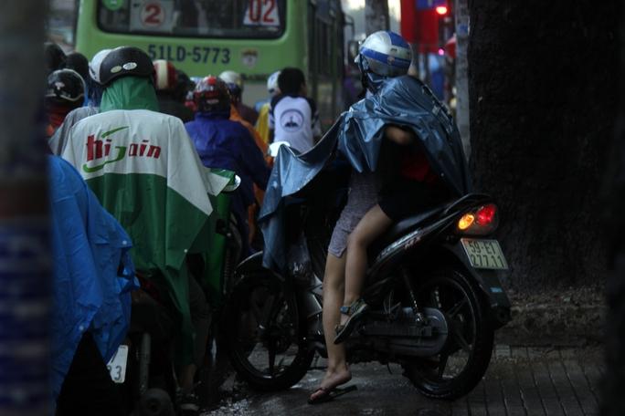 Một phụ nữ chở theo con nhỏ không thể đưa xe từ trên vỉa hè xuống đường bởi các phương tiện giao thông khác đang chen chúc kéo dài.