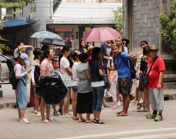 Hướng dẫn viên người Trung Quốc đang hướng dẫn cho khách Trung Quốc tại Nha Trang sáng 5-7 Ảnh: KỲ NAM