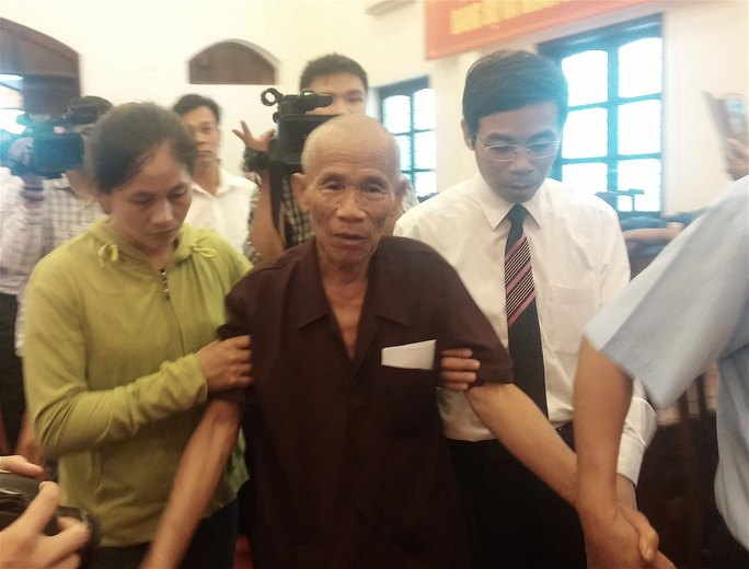 Ông Trần Văn Thêm được người thân dìu đến buổi lễ công bố quyết định đình chỉ điều tra bị can và công khai xin lỗi đối với ông