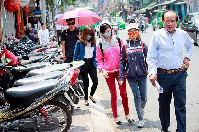 Người đi bộ phải xuống lòng đường Nguyễn Thị Minh Khai (quận 1) để lưu thông vì vỉa hè bị chiếm dụng làm nơi giữ xe Ảnh: QUỐC CHIẾN