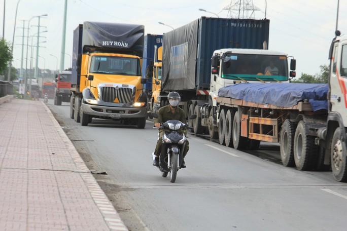 Nhiều tài xế container nóng lòng vào cảng đã lấn hẳn sang làn xe máy trên đường Vành đai 2 Ảnh: SỸ ĐÔNG