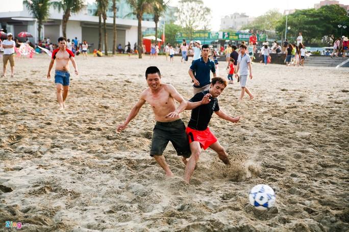 Nhóm thanh niên đang đá bóng ở khu vực bãi còn rộng.