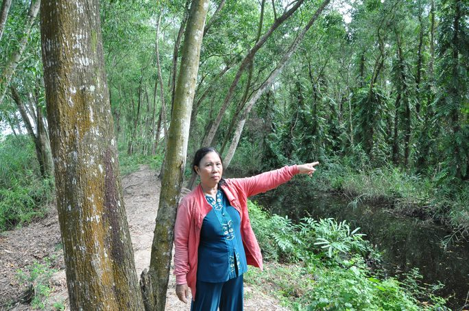Bà Phạm Thị Lang bên khu rừng do bà trồng, chăm sóc, bảo vệ nhưng không được khai thác, sử dụng