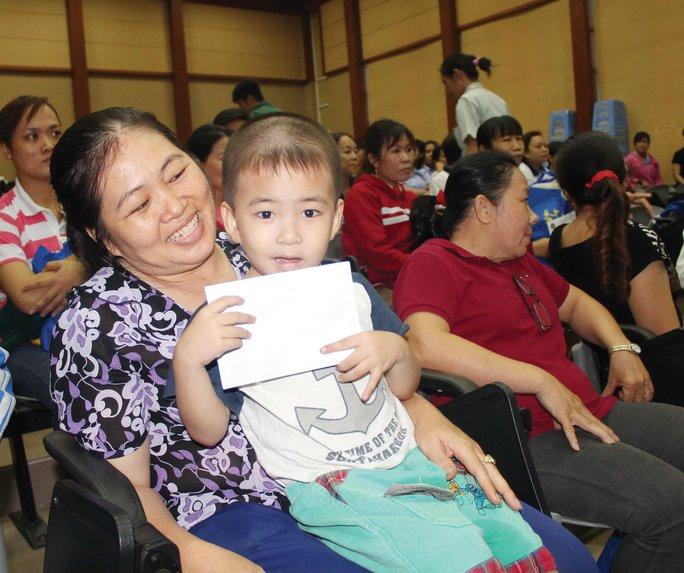 Mẹ con chị Trương Lệ Quyên, nguyên là công nhân Công ty TNHH Viva, vui mừng khi nhận được quà Tết Ảnh: THANH NGA