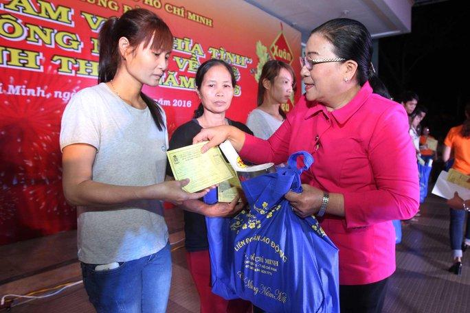 Bà Nguyễn Thị Bích Thủy, Phó Chủ tịch LĐLĐ TP HCM, tặng vé xe và quà Tết cho công nhân khó khăn tại các KCX-KCN TP Ảnh: HOÀNG TRIỀU