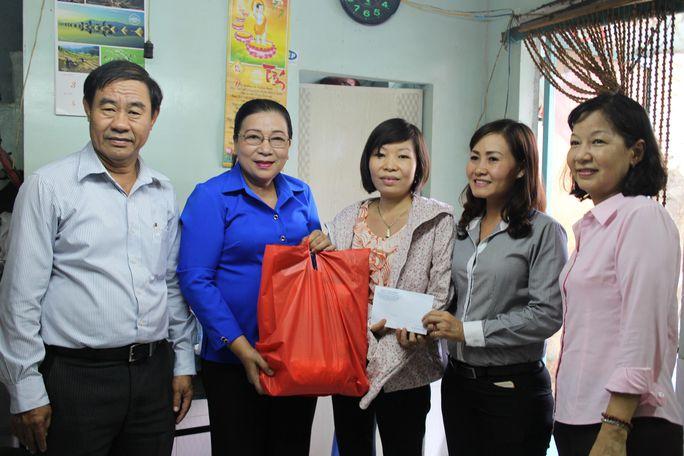 Bà Nguyễn Thị Bích Thủy (thứ hai bên trái), Phó Chủ tịch LĐLĐ TP HCM, tặng quà Lê Thị Khánh Toàn Ảnh: HỒNG ĐÀO
