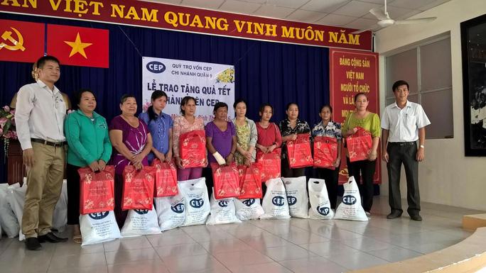Đại diện chi nhánh CEP quận 9 (bìa trái) tặng quà Tết cho thành viên khó khăn