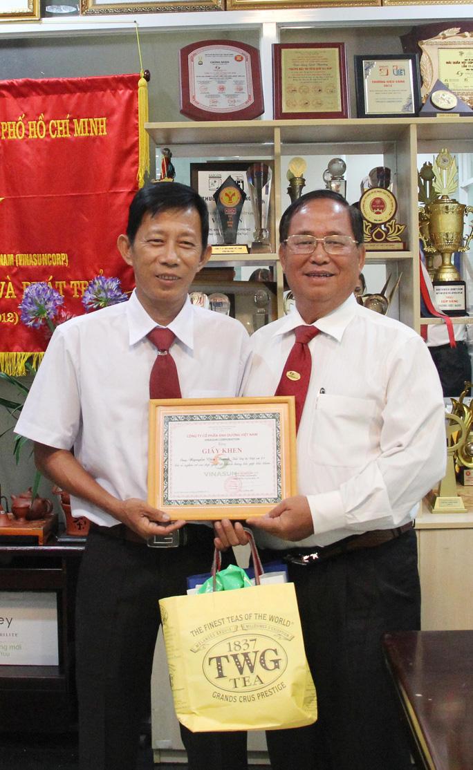 Ông Tạ Long Hỷ (bìa phải), Phó Tổng giám đốc Vinasun, trao giấy khen và tiền thưởng cho tài xế Nguyễn Văn Thanh