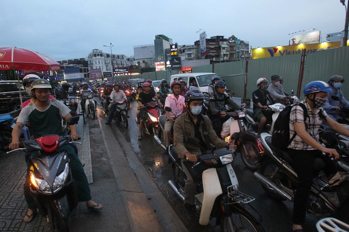 Người dân vất vả đi qua đoạn đường bị rào chắn, nhiều người dân phải lên lề để có thể di chuyển