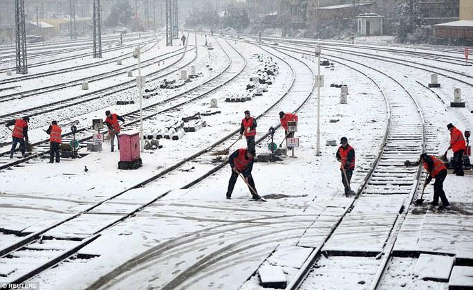 Công nhân dọn tuyết trên đường ray xe lửa ở TP Nam Xương, tỉnh Giang Tây. Ảnh: Reuters