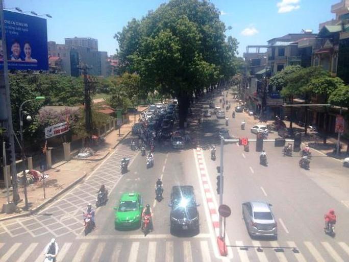 Người tham giao thông núp dưới bóng cây trốn nắng khi dừng đèn đỏ