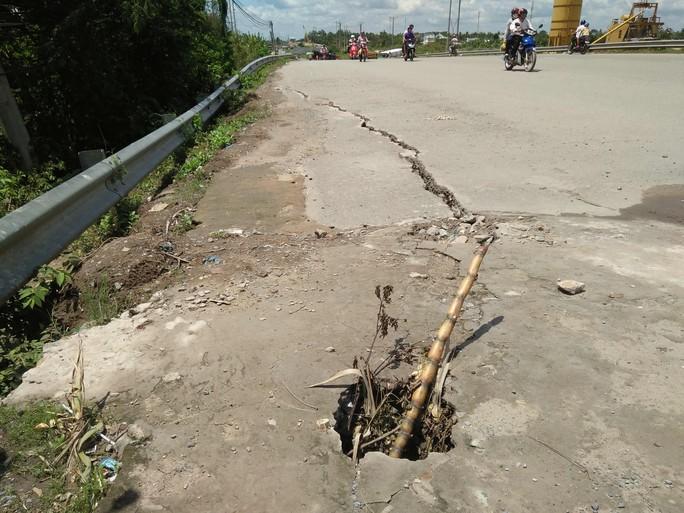 Điểm đấu nối giữa dốc và thân cầu Cái Sâu bị sụp một hố to, người dân dùng xi măng trám tạm và cắm cây cảnh báo người đi đường