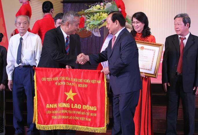 Ông Lê Thanh Hải, Ủy viên Bộ Chính trị, Chỉ đạo Đảng bộ TP HCM, trao cờ Anh hùng Lao động thời kỳ đổi mới cho lãnh đạo tổ chức CĐ các thời kỳ ẢNH: HOÀNG TRIỀU