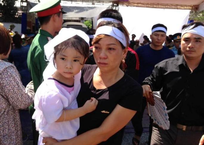 Chị Trần Thị Hà, vợ đại tá phi công Trần Quang Khải, bế con nhỏ trong tang lễ chồng sáng nay 20-6 tại nhà tang lễ Bệnh viện Quân y 4 ở TP Vinh, tỉnh Nghệ An - Ảnh: Đức Ngọc