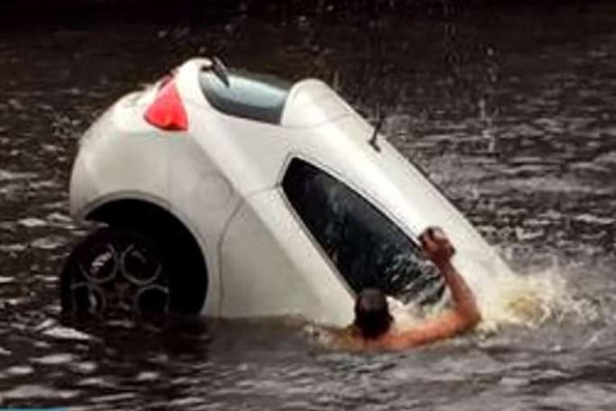 Những người giải cứu dùng đá, gạch và búa đập vỡ cửa kính sau xe hơi để cứu 2 mẹ con bị kẹt bên trong. Ảnh cắt từ clip YouTube