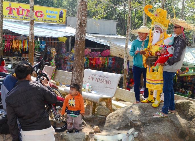 Nhiều du khách tỏ ra thích thú khi được chụp ảnh chung với thần tài bán vé số ở núi Cấm