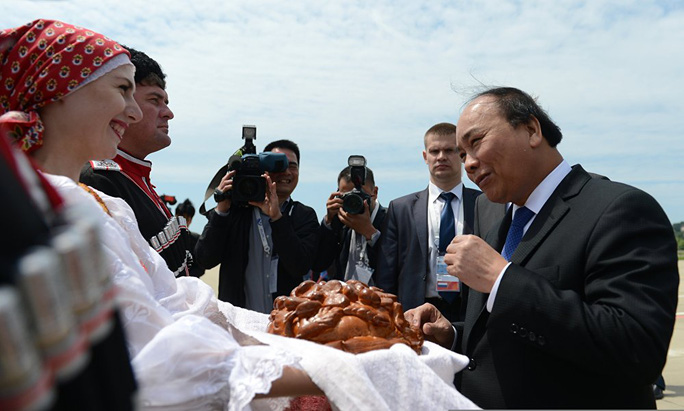 Thủ tướng nếm bánh mì để đáp lại lòng hiếu khách của đại diện nước chủ nhà Nga