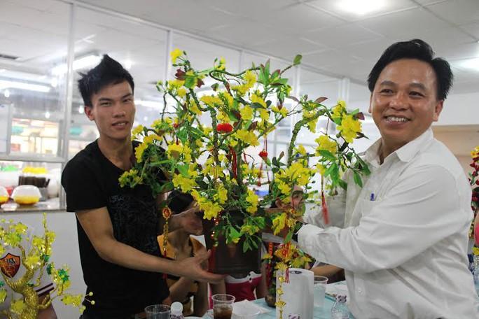 Ông Trần Vũ Bình - Phó Chủ tịch LĐLĐ quận 1, TP HCM - tặng cành mai cho công nhân không có điều kiện về quê ăn Tết của Công ty CP Thực phẩm Trung Sơn