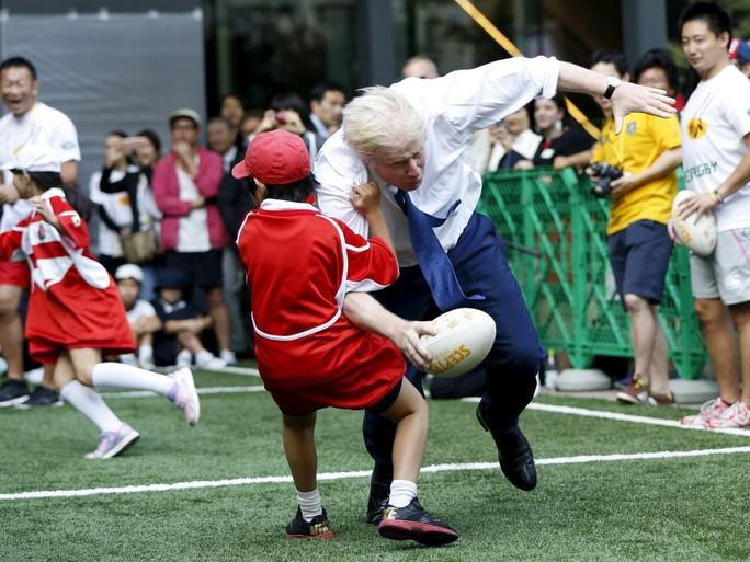 Ông Johnson húc ngã một cậu bé 10 tuổi trong trong trận đấu bóng bầu dục với một nhóm trẻ em Nhật ở Tokyo. Ảnh: Reuters