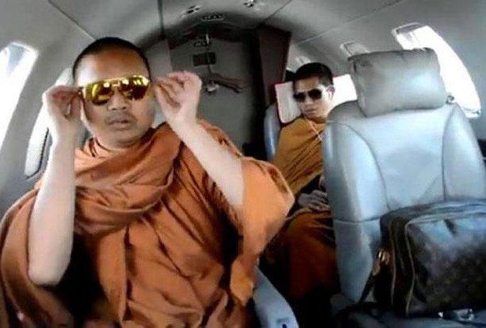 Ảnh chụp lại từ video clip cho thấy nhà sư Wirapol đi du lịch bằng máy bay riêng và dùng túi xách và kính mát hàng hiệu. Ảnh: Bangkok Post