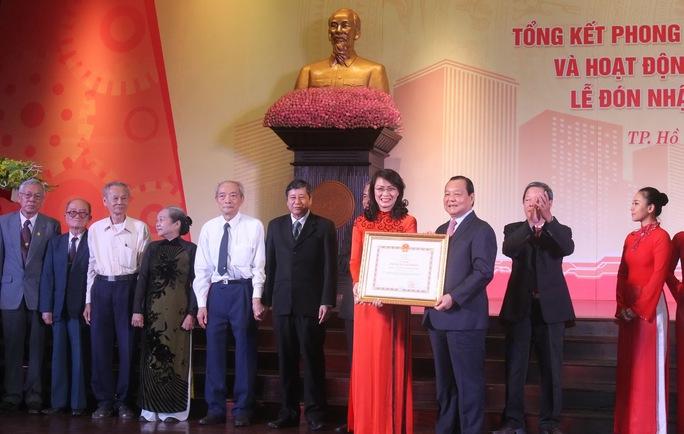 Ông Lê Thanh Hải-Ủy viên Bộ Chính trị, Chỉ đạo Đảng bộ TP HCM, trao danh hiệu Anh hùng Lao động thời đổi mới cho lãnh đạo LĐLĐ TP HCM  ẢNH: HOÀNG TRIỀU