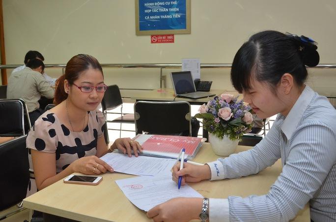 Nhân viên Ngân hàng Đông Á hướng dẫn thủ tục vay vốn cho doanh nghiệp Ảnh: Tấn Thạnh