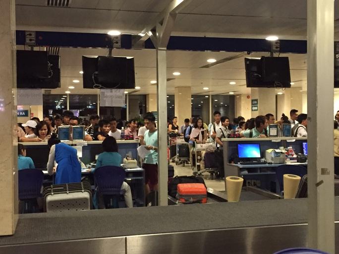 Hành khách kiên nhẫn ổn định trật tự làm thủ tục tại sân bay Tân Sơn Nhất khi hệ thống mạng bị tấn công vào ngày 29-7 Ảnh: BẢO NGỌC
