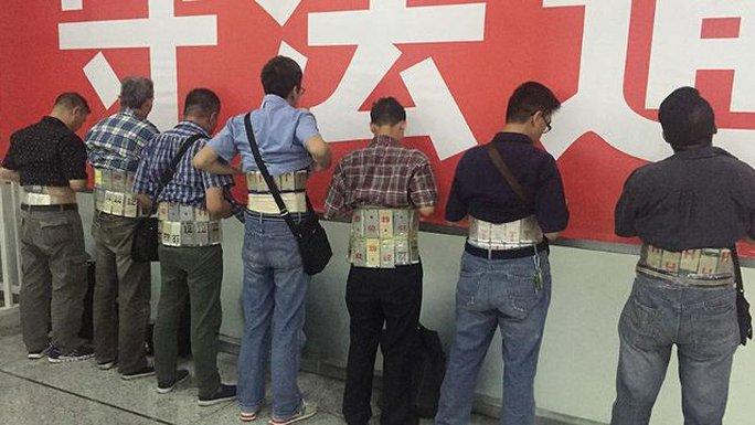 7 người đàn ông bị bắt với 580 chiếc điện thoại di động dán chằng chịt trong người. Ảnh: Weibo