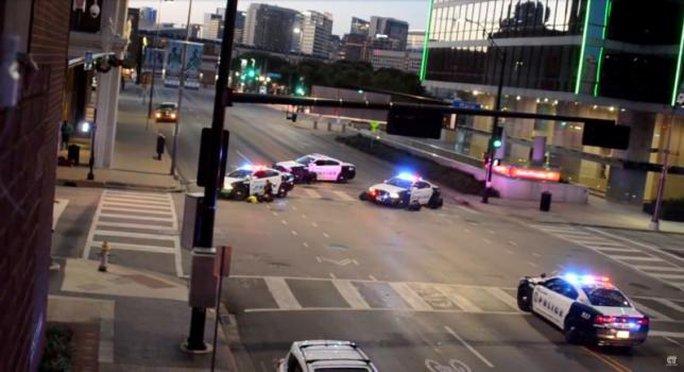 Cảnh sát nấp sau xe tuần tra khi bị tấn công đêm 7-7. Ảnh: Reuters