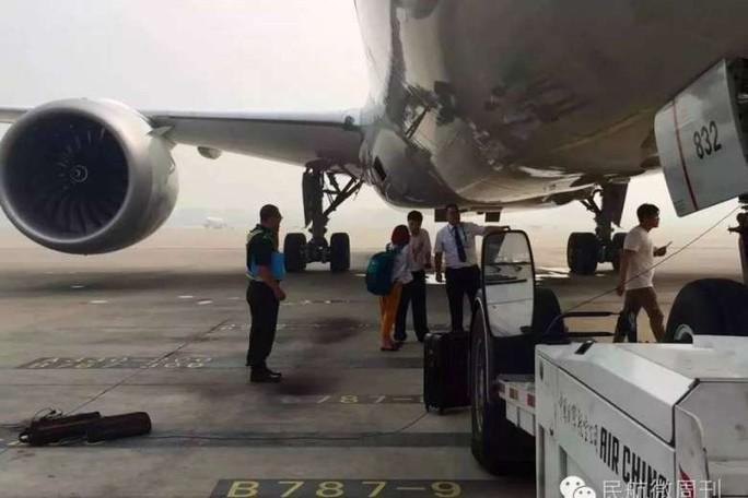 Người phụ nữ cố thuyết phục nhân viên sân bay để được lên máy bay. Ảnh: China Daily