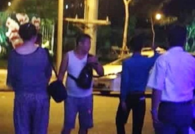 Người mặc áo trắng (giữa) có hành vi đốt tiền Việt Nam ở quán bar tại Đà Nẵng. Ảnh do bảo vệ quán bar cung cấp.
