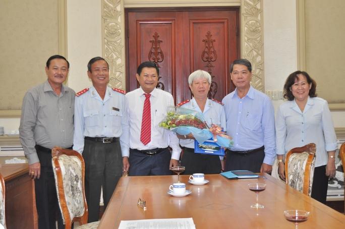 Ông Trần Đình Trữ (cầm hoa) nhận quyết định làm Phó Chánh Thanh tra TP