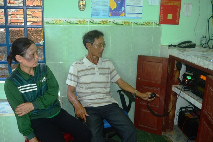 Bà Nguyễn Thị Năng, vợ ngư dân Võ Văn Lựu ngồi bên máy icom cộng đồng chờ tin tức. Ảnh: T.Trực